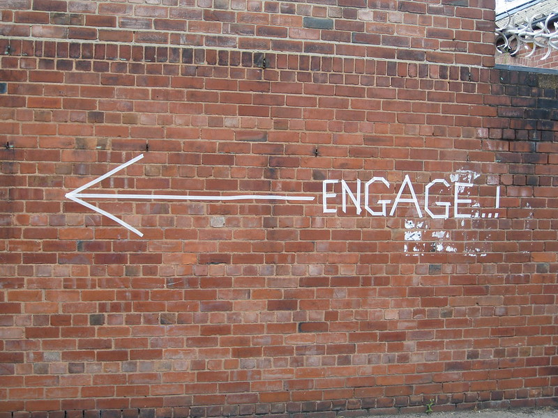 """An arrow, pointing left, and the word """"enGAGE!"""" on a brick wall"""